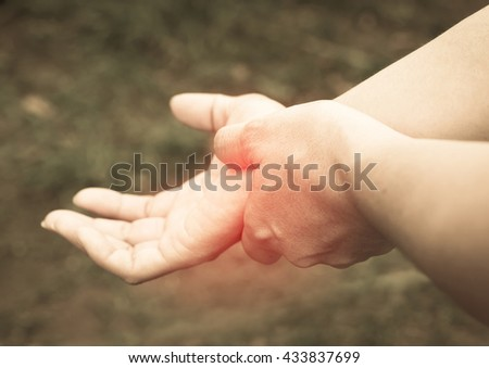 women acute pain in a wrist, holding hand to spot of wrist pain. - stock photo