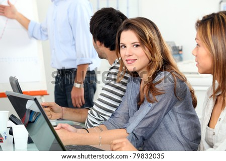 women and a man behind computers and listening at a meeting or vocational training - stock photo