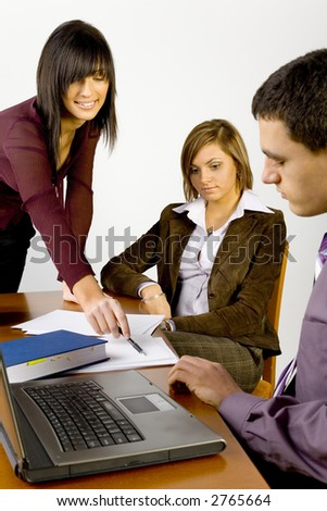 Women and a man having conversation at conference's table. Standing woman's  showing something on the paper. - stock photo