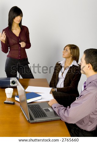 Women and a man having conversation at conference's table. There're multimedia projector and laptop on it.