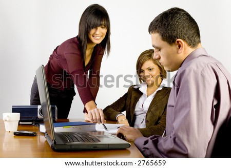 Women and a man having conversation at conference's table. There's multimedia projector and laptop on it. - stock photo
