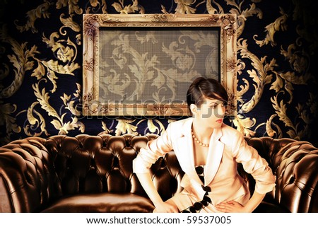 women and brown leather couch with empty frame in minimalist interior - stock photo