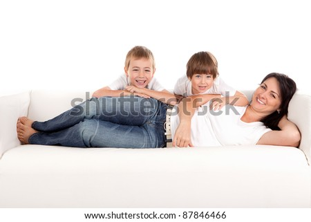 Women and children lying on a white sofa.  White background - stock photo