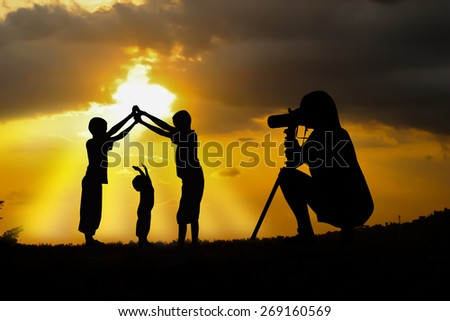 women and her boys play at sunset. - stock photo