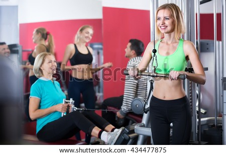 Women and man doing powerlifting on machines in gym