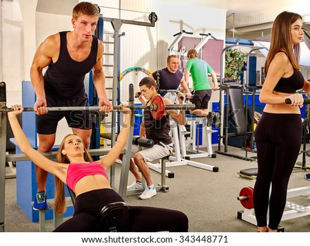 Women and men hard working  on different  simulator at gym. She lifting barbell. - stock photo