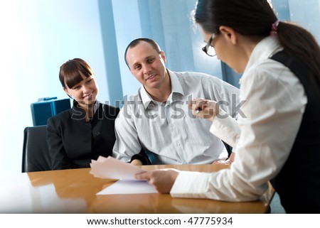 Women and men with girl in black jacket at table - stock photo