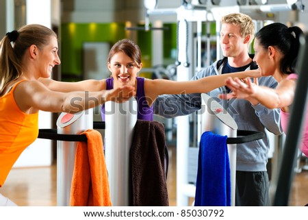 women and trainer in gym in front of a exercising machine doing fitness exercises