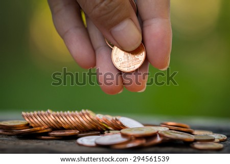 Women are collecting coins Gold for the future. Natural green background. - stock photo