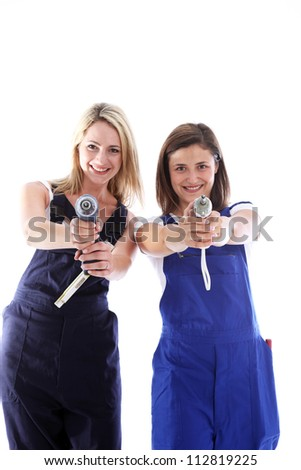 Women artisans taking aim Humorous image of two attractive women artisans having fun taking aim at the camera with their handheld power tools - stock photo