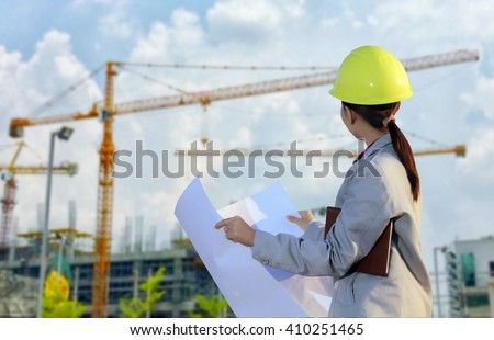 women asia engineer working and holding blueprints at construction site