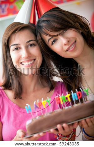Women at a birthday party holding the cake and smiling - stock photo