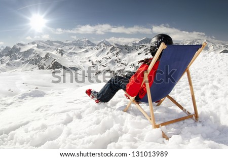 Women at mountains in winter lies on sun-lounger,France high mountains - stock photo