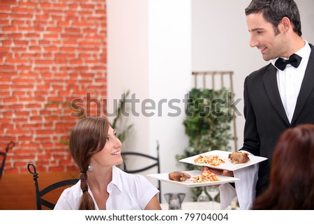women at restaurant with waiter - stock photo