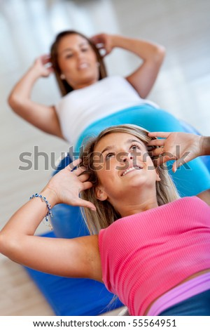 Women at the gym doing exercises for their abs - stock photo