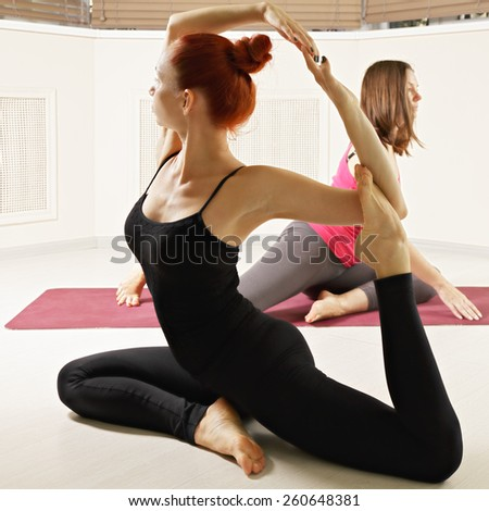 Women at yoga class instructor showing new pose - stock photo