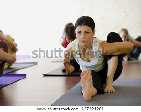 Women at yoga class stretching - stock photo