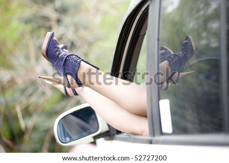 Women beautiful legs in high heel shoes, car window