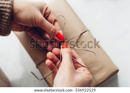 Women binds classic bow for gift - stock photo