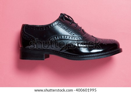 women brogue shoe on a pink background with shadows