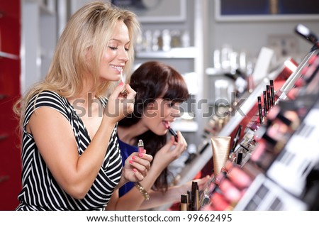 Women buying and testing cosmetics in a beauty store - stock photo