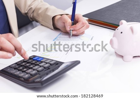 Women calculate expenses with calculator and piggybank - stock photo