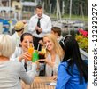 Women celebrating with cocktails at harbor restaurant - stock photo