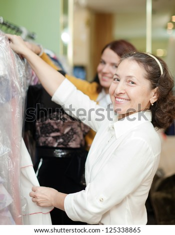 women chooses  dress at shop of fashionable clothes - stock photo