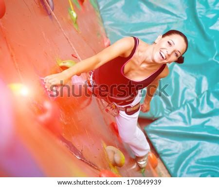 women climbing on a wall in an outdoor climbing center - stock photo