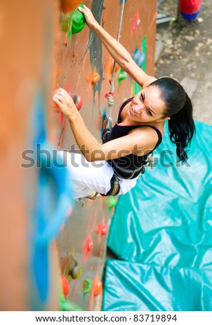 women climbing on a wall in an outdoor climbing center - stock photo