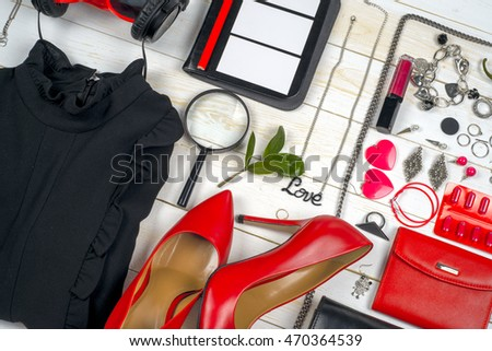 Women clothing set and accessories on white wooden background. Red and black. Top view,