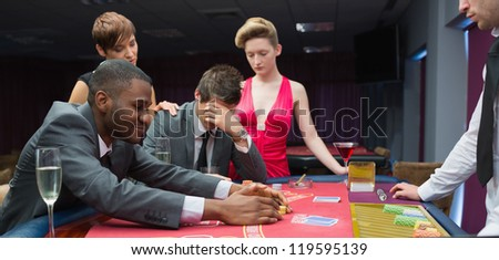 Women comforting man as other man takes jackpot at poker in casino - stock photo
