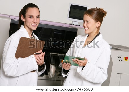 Women computer technicians working on computer parts in the lab - stock photo