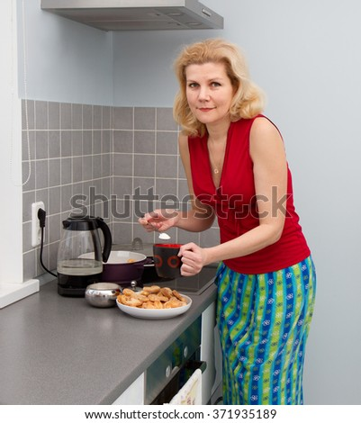 Women cooking tea at domestic kitchen - stock photo