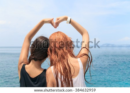 Women couple forming heart shape with arms at the sea