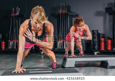 Women couple training over steppers in aerobic class - stock photo