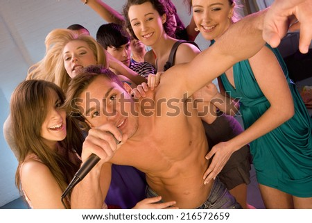 Women dancing behind bare chested man singing into microphone