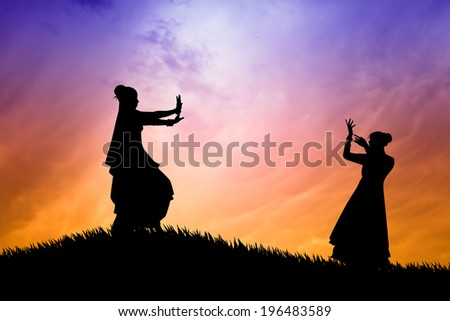 Women dancing indian dance at sunset - stock photo