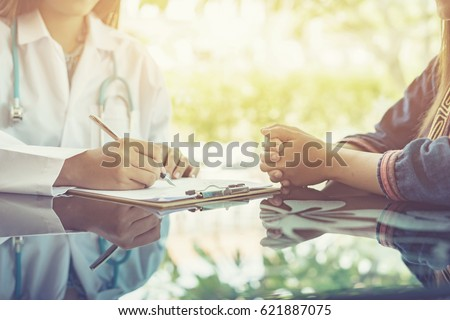 Women Doctors and patient are discussing something ,Having Consultation,Medical Pretty Doctor working in hospital writing a prescription, Healthcare and medically concept,selective focus