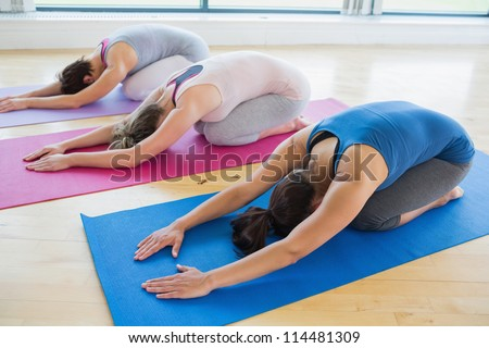 Women doing childs pose in yoga class in fitness studio - stock photo