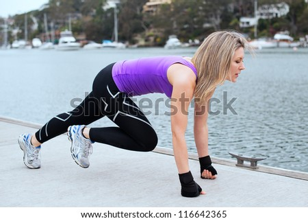 Women doing pull ups outdoors close to the water - stock photo