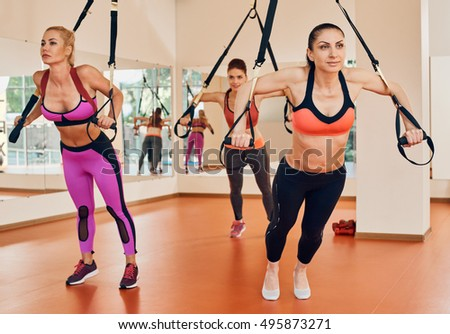 women doing push ups training arms trx