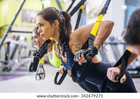 Women doing push ups training arms with trx fitness straps in the gym Concept workout healthy lifestyle sport - stock photo