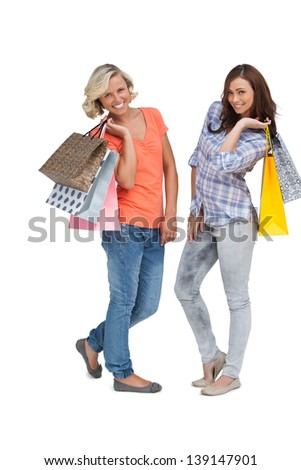 Women doing shopping and holding bags on white background - stock photo
