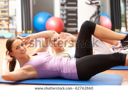 Women Doing Stretching Exercises In Gym - stock photo