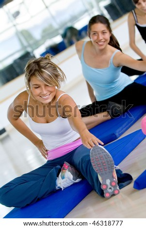 Women doing stretching exercises on the floor at the gym