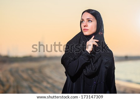 Women dressed middle eastern way poses on sunset background. - stock photo