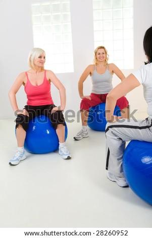 Women dresset sportswear working out on fitness ball. - stock photo