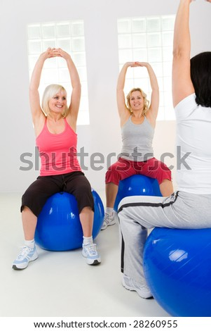 Women dresset sportswear working out on fitness ball. They have raised hands.