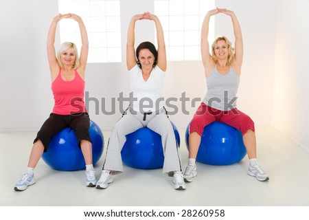 Women dresset sportswear working out on fitness ball. They have raised hands. They're smiling and looking at camera. Front view. - stock photo